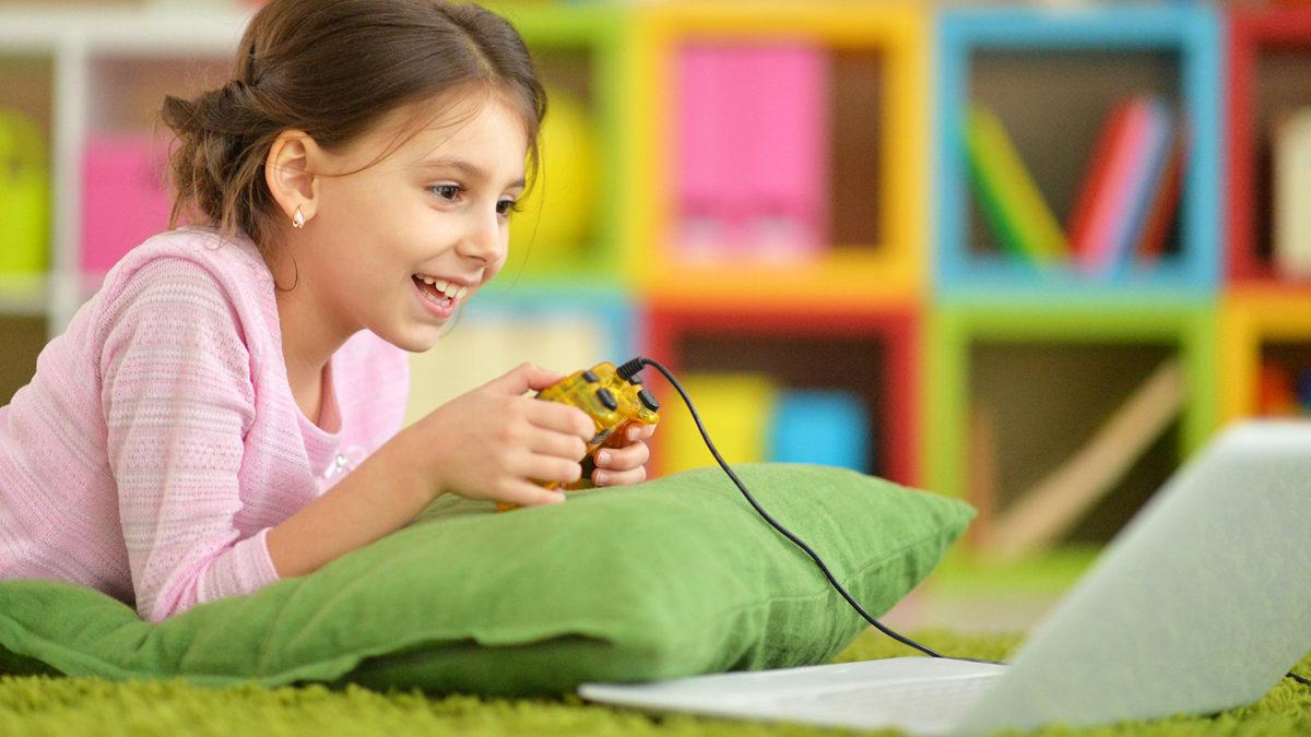 Liten jente som ligger på golvet og holder en spillkonsoll i hendene og ser på en bærbar datamaskin (Foto: colourbox.com)