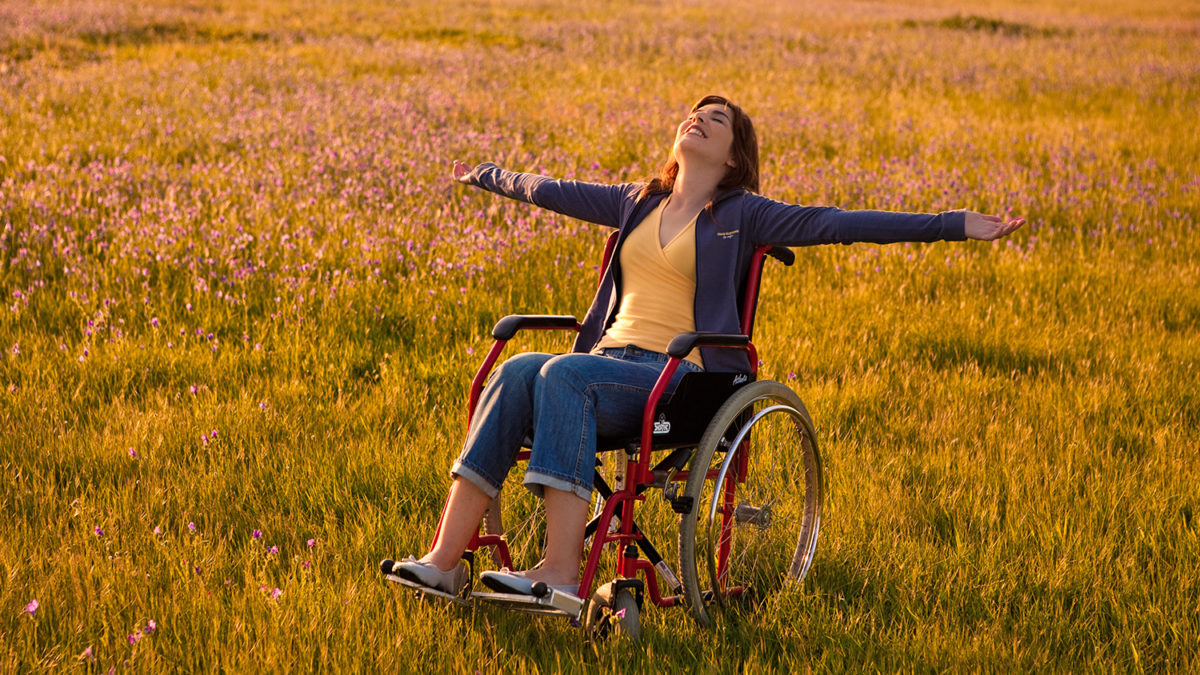 Glad kvinne i rullestol på en blomstereng (Foto: colourbox.com)