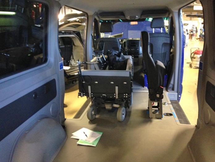 Liggende transport i bil hvor sengen er montert på et understell på en elektrisk rullestol