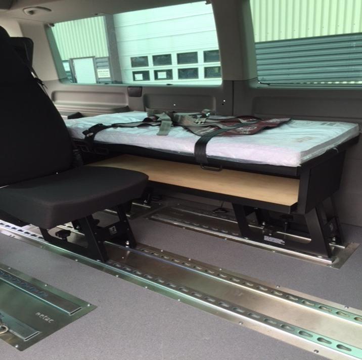 Liggende transport hvor sengen er montert på understell som sitter fast i skinner i gulvet