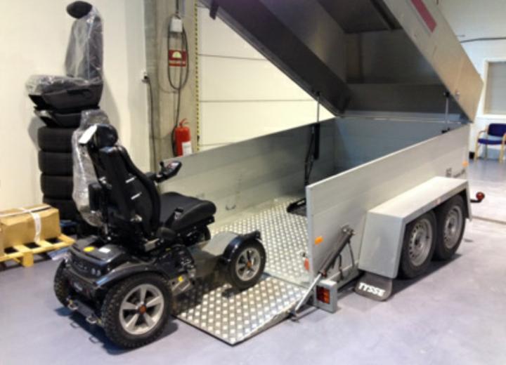 Elektrisk rullestol på kjøreskinne til tilhenger med kapell