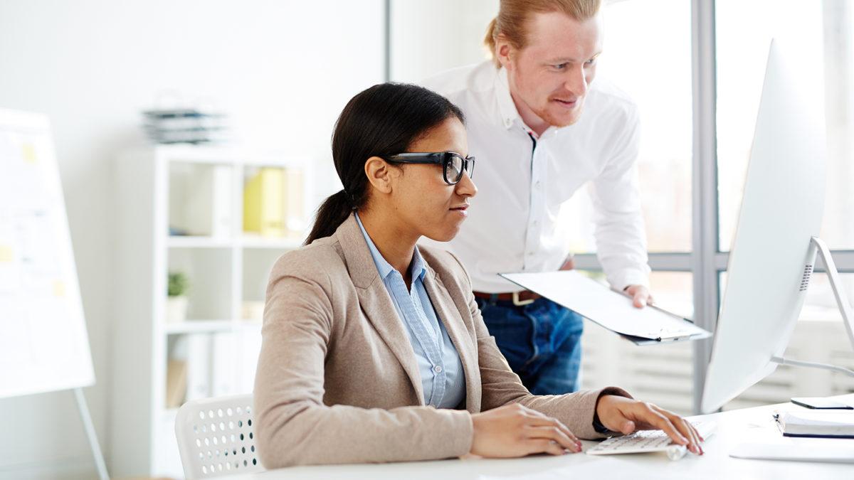 En kvinnelig og mannlig kollega som jobber foran en dataskjerm (foto: colourbox.com)