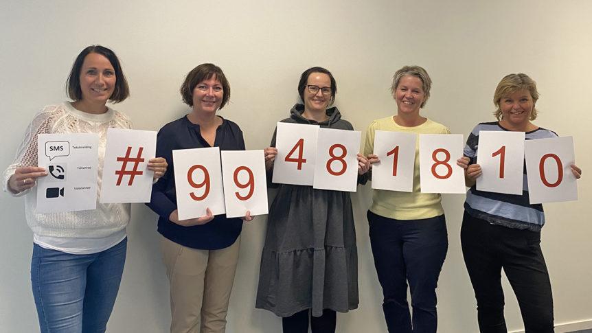 Fem tolker som viser holder ark som viser det nye nasjonale telefonnummeret ved akutt behov for tolk
