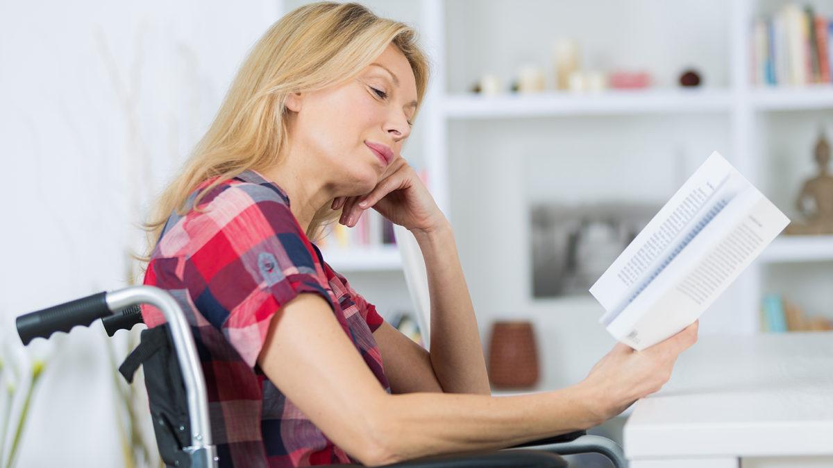Kvinne som sitter i en rullestol og leser en bok (Foto: colourbox.com)