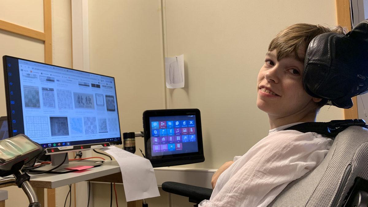 Amalie sitter i rullestolen sin og arbeider med pc-en