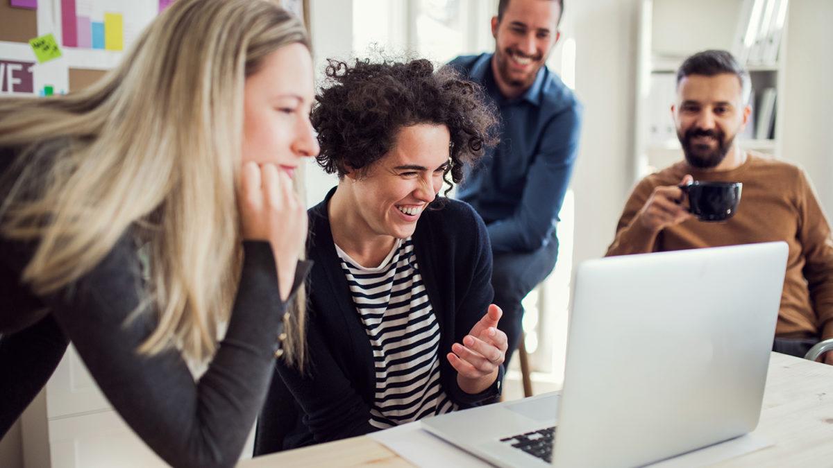 Fire fornøyde kollegaer som ser på en dataskjerm (foto: colourbox.com)
