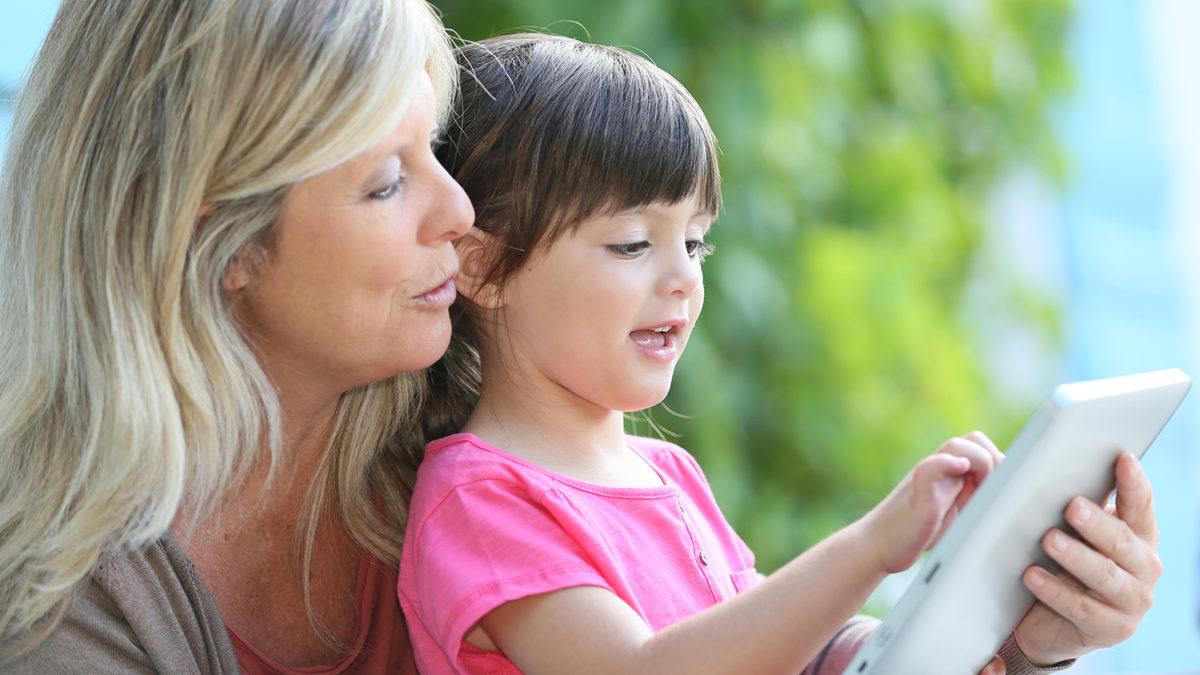 En liten jente med nettbrett på fanget til en dame (foto: colourbox.com)