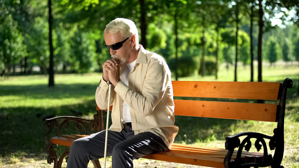 En tankefull blind mann som sitter alene på en benk i parken (foto: colourbox.com)