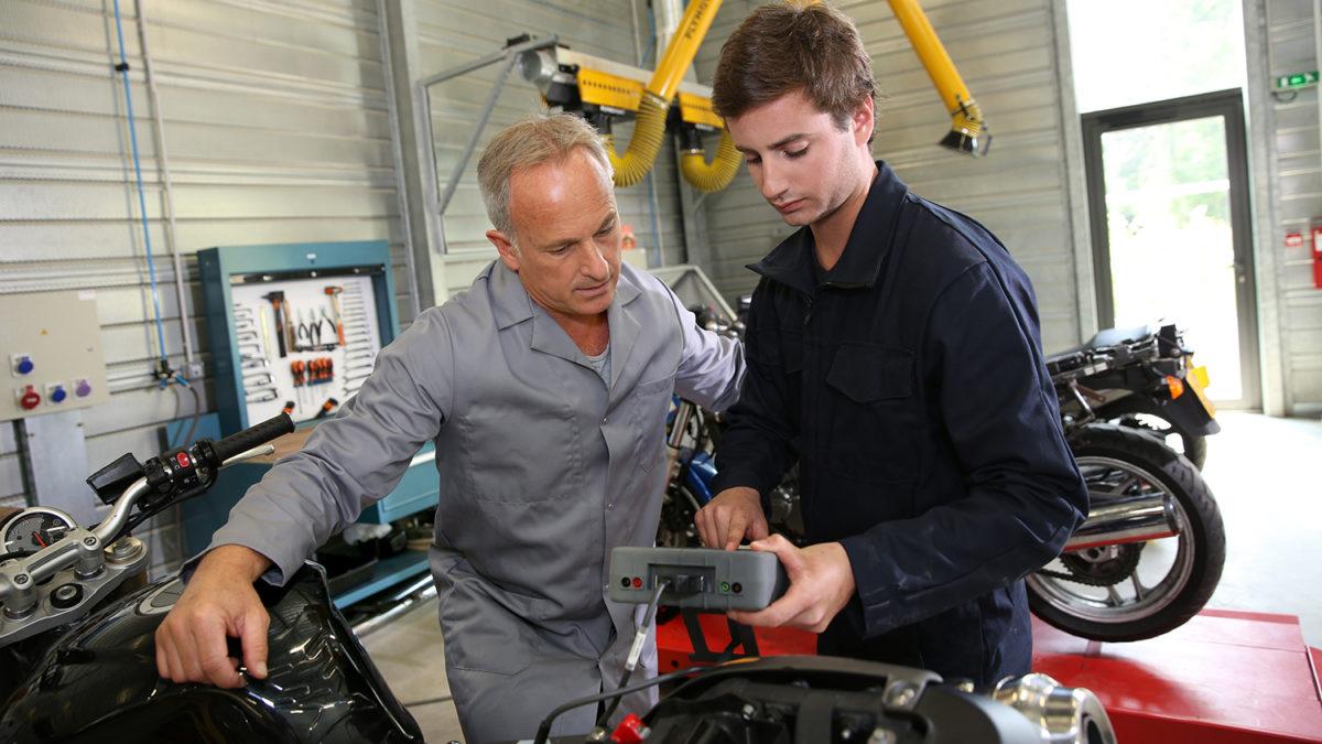 En ung og en eldre mann i arbeidsklær på et motorsykkelverksted (foto: colourbox.com)