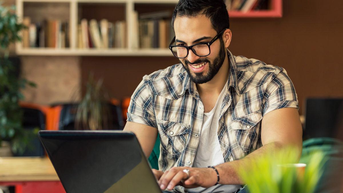 Smilende mann foran bærbar datamaskin på et bord i stua (foto: colourbox.com)