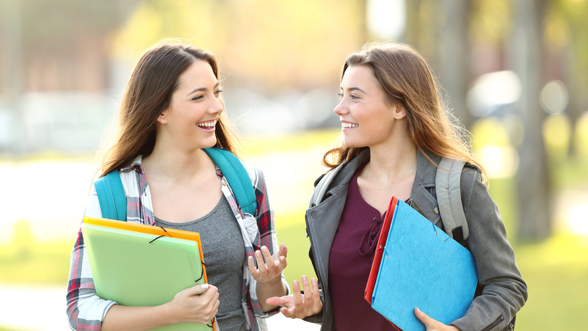 To smilende unge kvinnelige studenter som er ute og går (foto: colourbox.com)