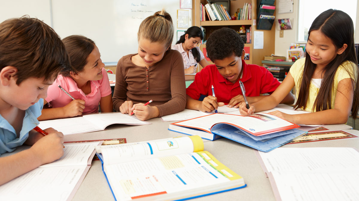 Fem elever som arbeider sammen rundt et bord i klasserommet (foto: colourbox.com)