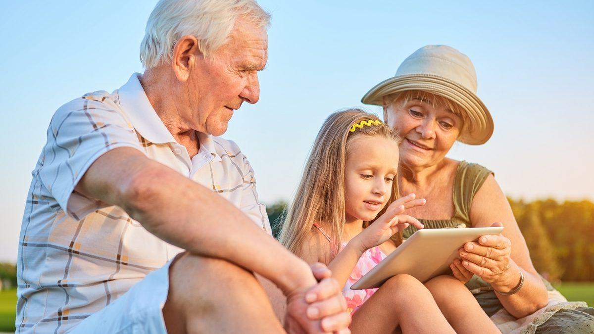 Ung jente med nettbrett som sitter på bakken med en gammel mann og dame på hver sin side av seg (foto: colourbox.com)