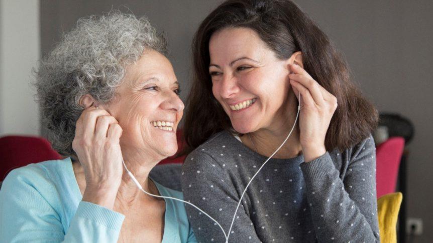 En eldre og en yngre dame som smiler til hverandre mens de lytter til samme lydbok (Copyright: Shutterstock / NLB)