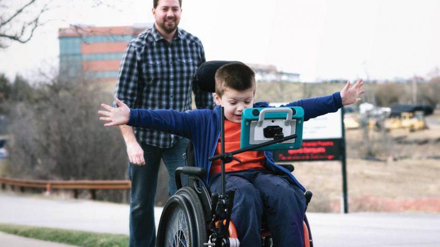 Gutt som sitter i rullestol og bruker talemaskin (Foto: Tobii Dynavox)