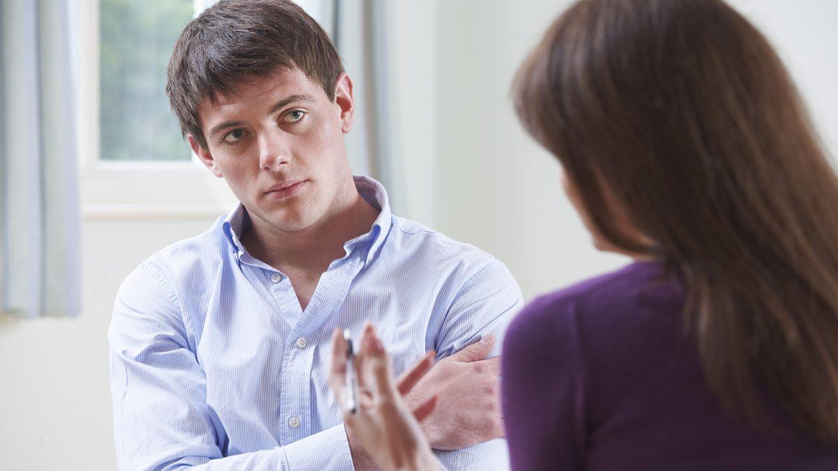 Trist ung mann som snakker med en rådgiver (Foto: colourbox.com)