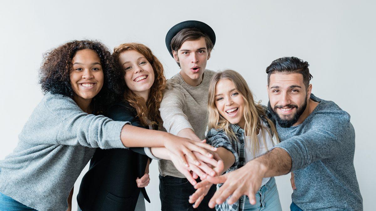 Bilde av fem smilende unge mennesker som strekker armene frem (foto: colourbox.com)