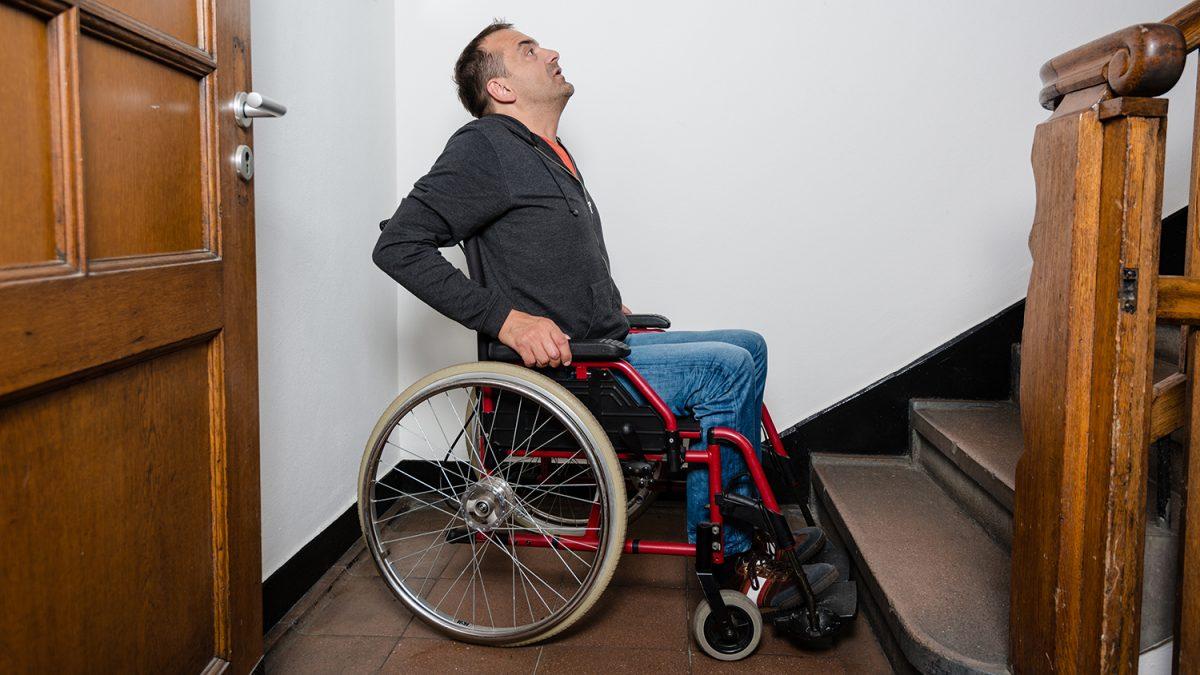En mann i rullestol som er ved bunnen av en innendørs trapp og ser oppover trappen