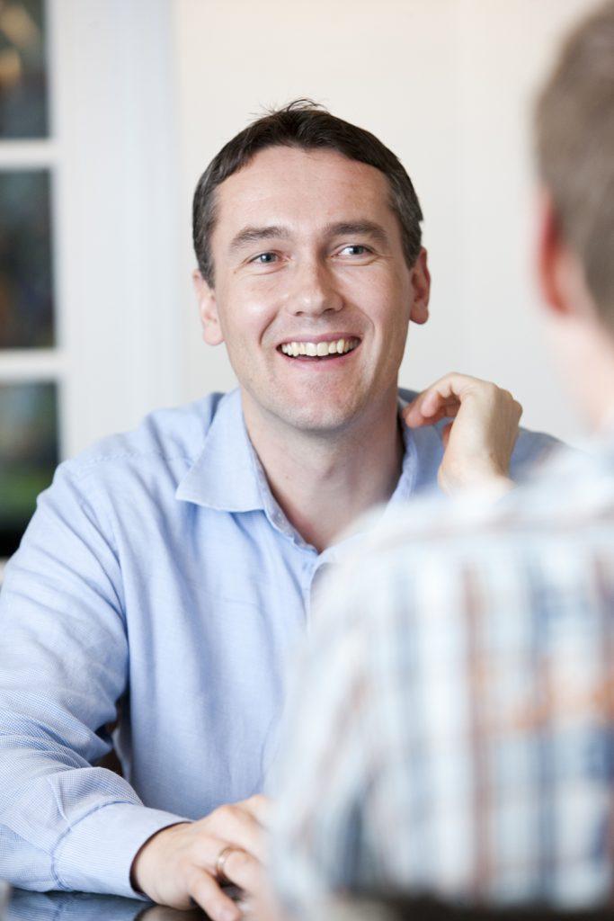 Smilende mann i samtale med en annen mann med ryggen til (foto: colourbox.com)