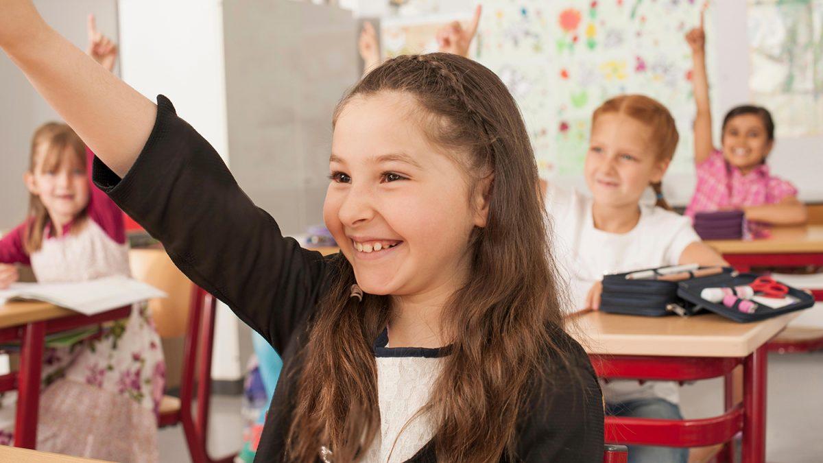 Smilende jente med langt brunt hår som rekker opp hånden i klasserommet (foto: colourbox.com)