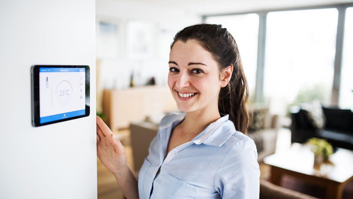 Smilende kvinne ved vegghengt kontrollpanel for smarthusteknologi (foto: colourbox.com)