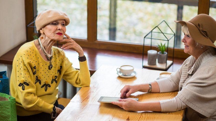 To eldre damer og et nettbrett ved et kafebord nær vinduet (foto: colourbox.com)