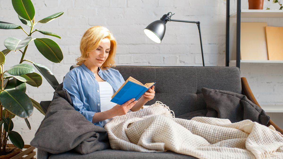 Ung kvinne under et teppe som sitter i en sofa og leser en bok (foto: colourbox.com)