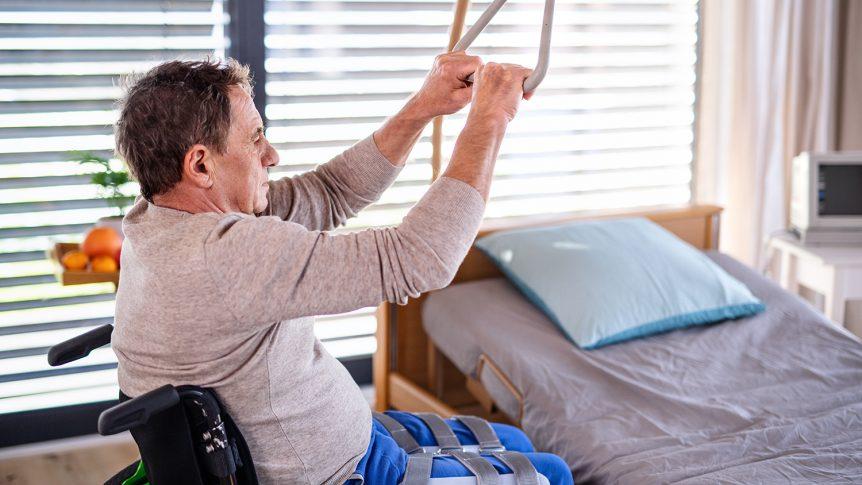 Eldre mann i rullestol som holder i en løftebøyle og skal flytte seg over til seng (foto: colourbox.com)