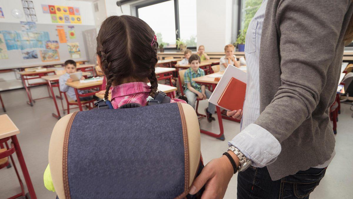 Kvinnelig lærer ønsker en ny elev velkommen foran de andre elevene i klasserommet (foto: colourbox.com)
