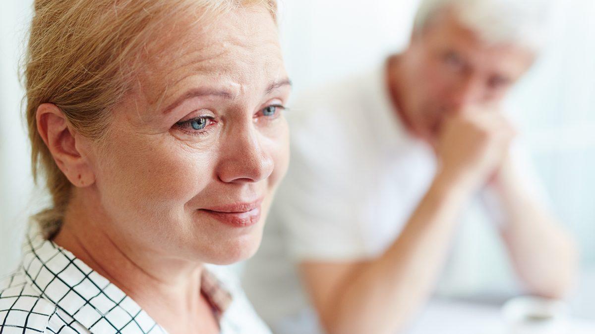 Nærbilde av en trist eldre dame i forgrunnen og en uklar mann i bakgrunnen (foto: colourbox.com)