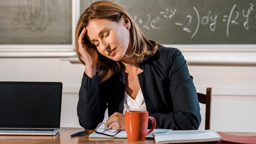 Sliten kvinnelig lærer med øynene lukket som sitter ved pulten i klasserommet (Foto: Colourbox.com)
