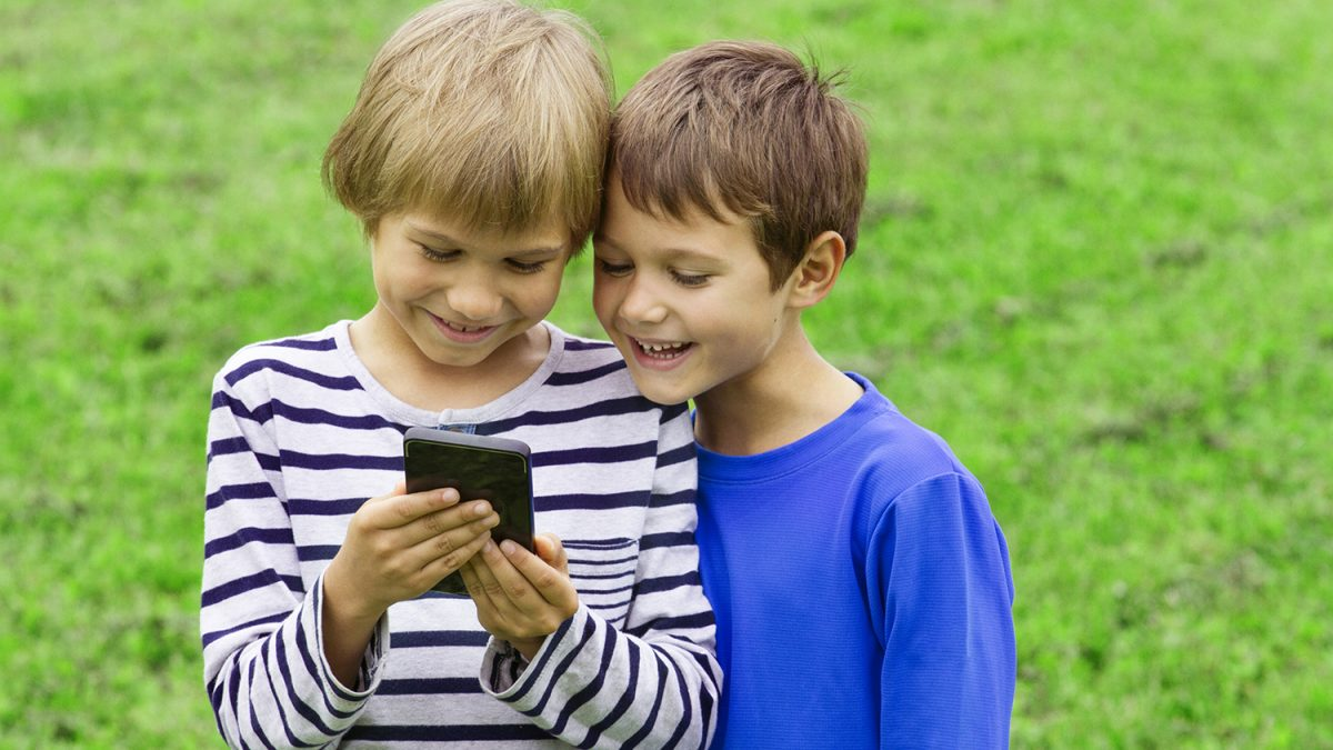 To smilende gutter som ser på en smarttelefon (Foto: colourbox.com)