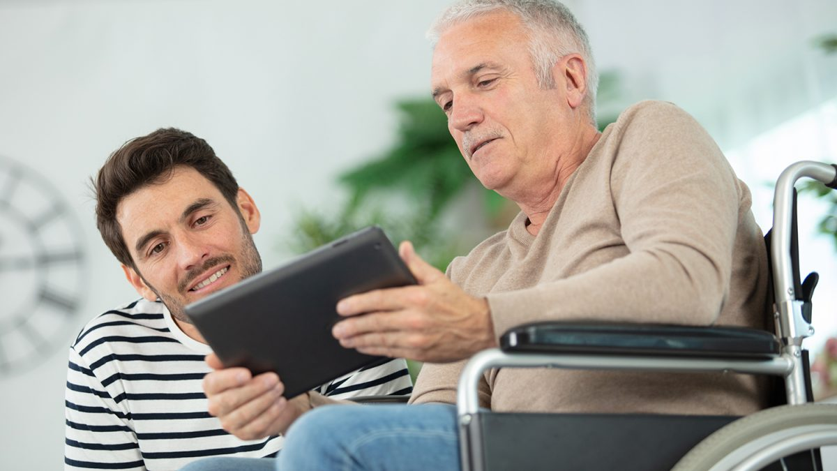 Mann i rullestol viser en annen mann på huk noe på et nettbrett (Foto: colourbox.com)