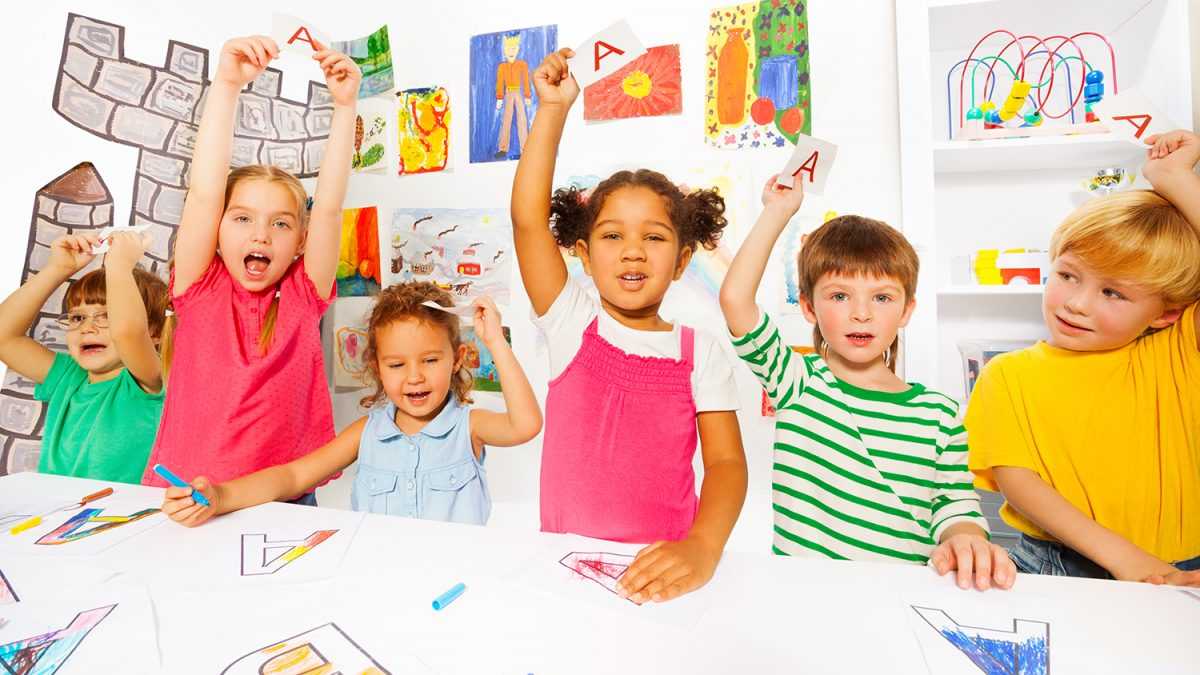 Seks smilende elever i et klasserom (Foto: colourbox.com)