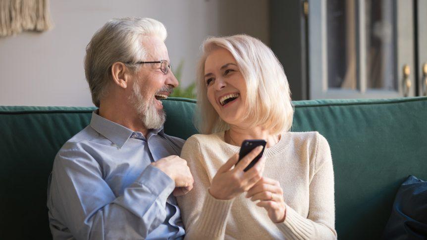 Smilende eldre mann og dame som sitter i en sofa og ler mens de bruker en smarttelefon (foto: colourbox.com)