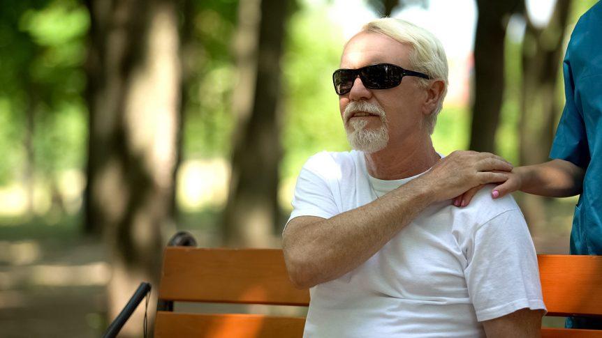 Eldre mann med mørke briller som sitter på en benk i parken (Foto: colourbox.com)