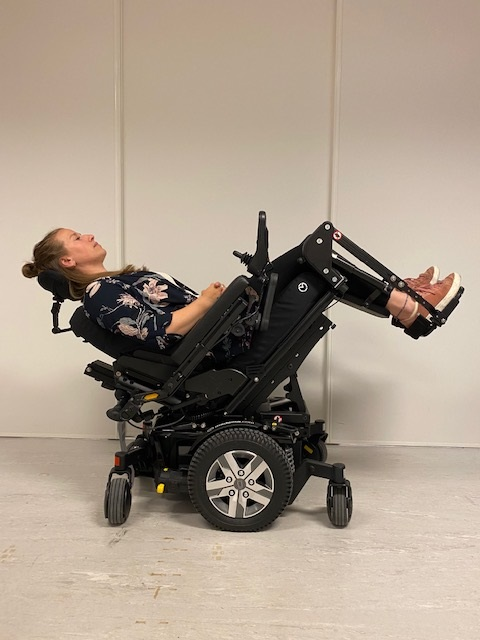 Kvinne som sitter i en bakovertiltet rullestol