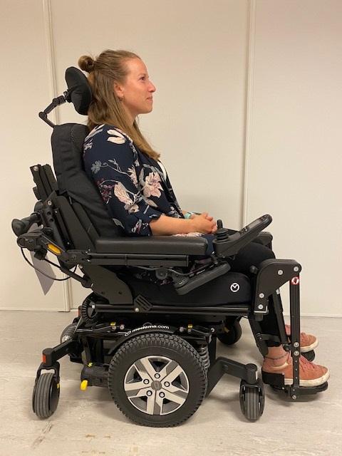 Kvinne som sitter i en nøytralt tiltet rullestol