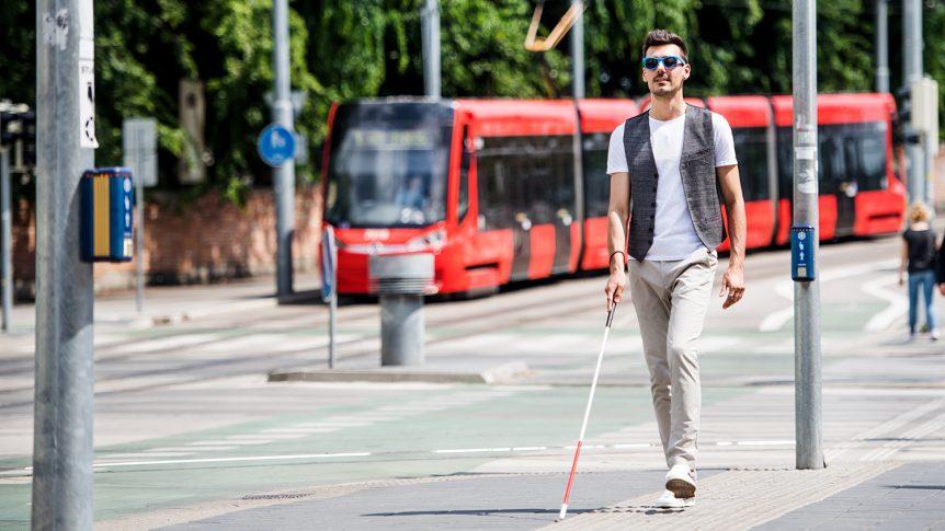 Mann med mørke briller og blindestokk som går alene i et trafikkert miljø (Foto: colourbox.com)