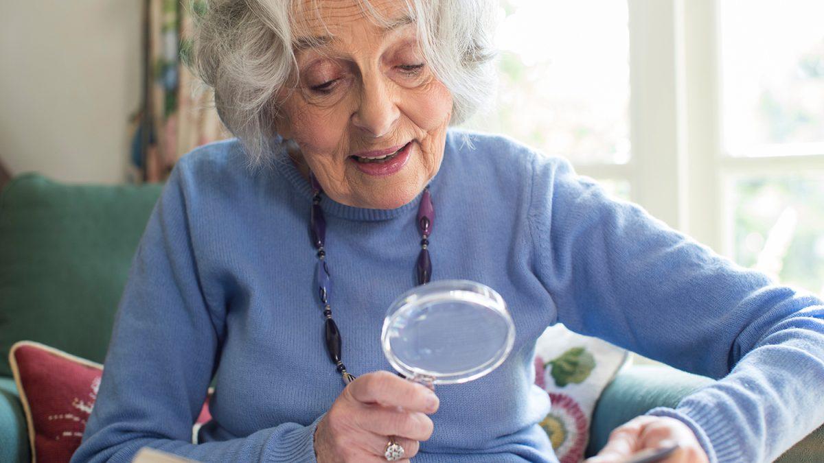 Eldre dame med grått hår som bruker lupe for å lese en tekst (Foto: colourbox.com)